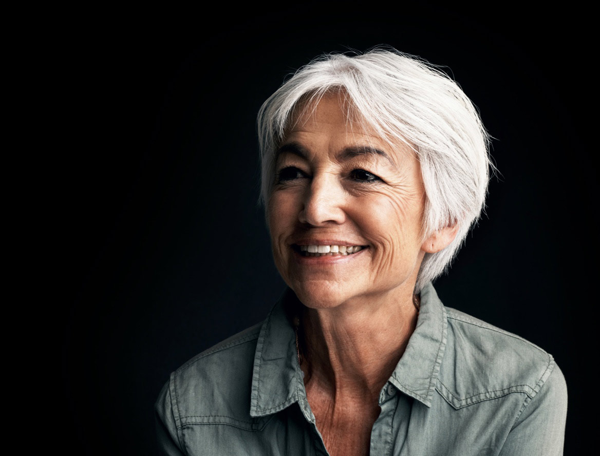 Profile view of a women with grey hair smiling on a black background.